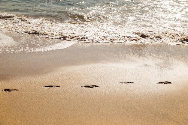 ビーチの砂の上の足跡パス