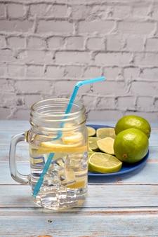 レモンとライムのいくつかのスライスの横にある氷とレモネードのピッチャーのビュー