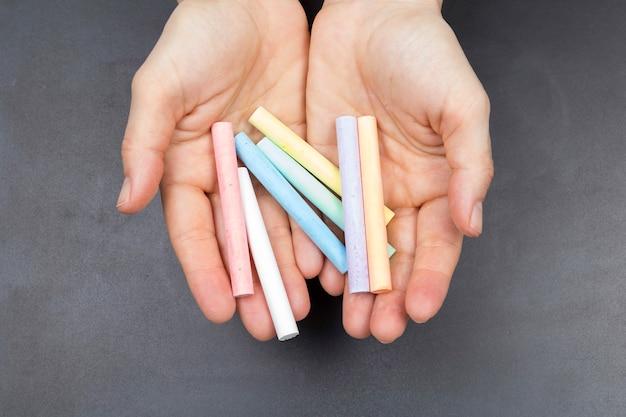 いくつかの色のチョークを保持している女性の手