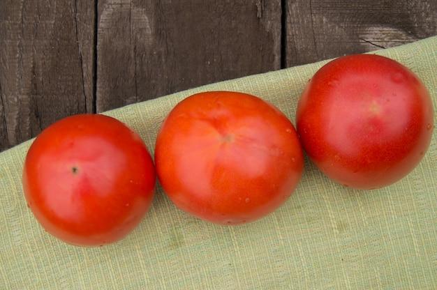 Свежие, спелые помидоры на салфетке, темный деревянный фон
