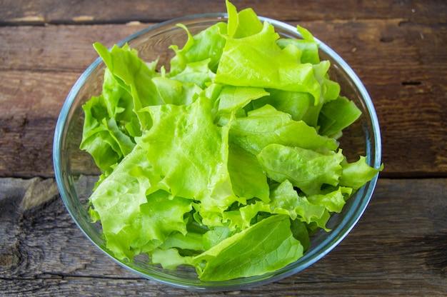 暗い背景の木のガラスのボウルに健康的なサラダ