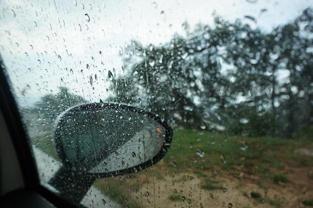 大きな雨滴が車のフロントガラス、車からの眺めを流れます。