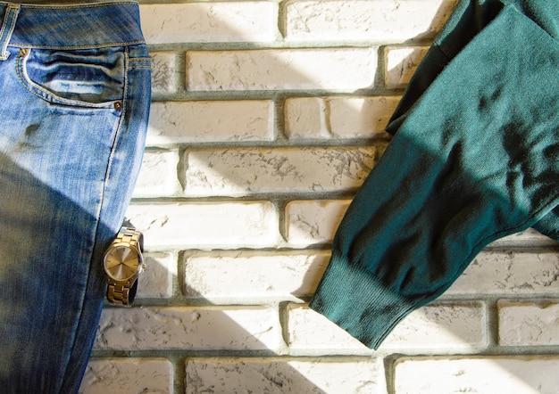 Современная повседневная мужская одежда и аксессуары на фоне белого кирпича, солнечного света