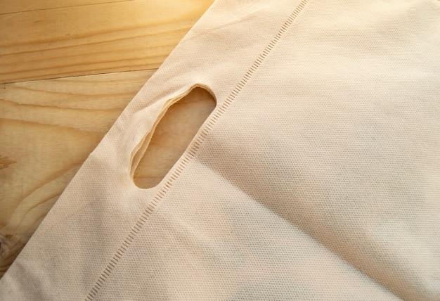 Концепция отказа от полиэтиленовых пакетов, эко-сумка из нетканого полотна, плоская планировка на светлом деревянном фоне