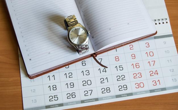 Мужские наручные часы на дорогом личном дневнике в кожаном чехле, рядом с календарем с датами, деловыми вещами и аксессуарами