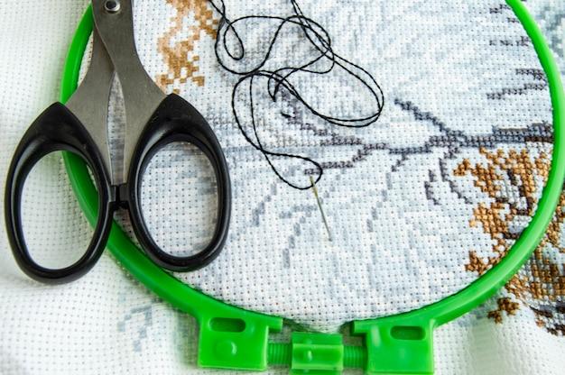 Плоская прокладка холста с красивым рисунком из ярких швейных ниток, ножниц и иголки для вышивания крупным планом