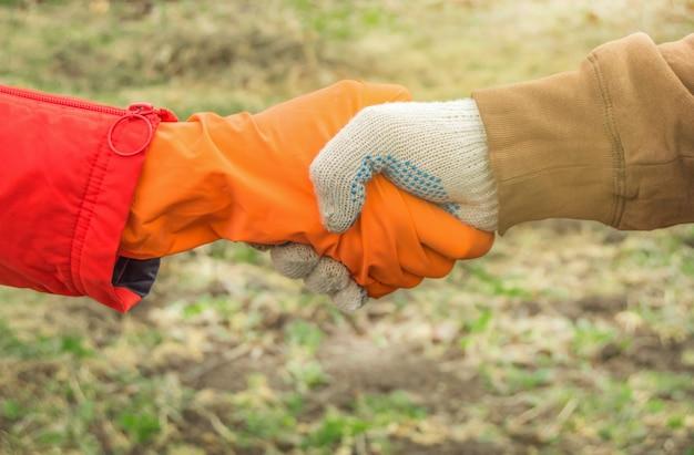 春の草を背景に戸外で防護手袋をした農家の握手。コロナウイルスと緊急時に安全を確保する