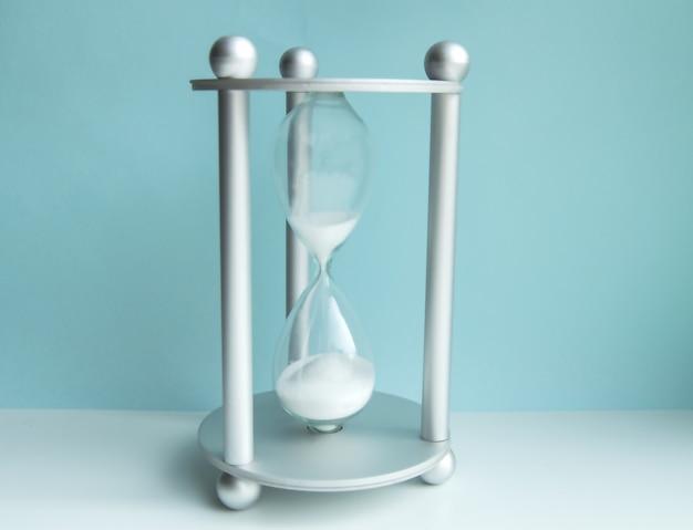 青い壁に砂時計。時間管理、締め切り、ビジネスのバランスの概念