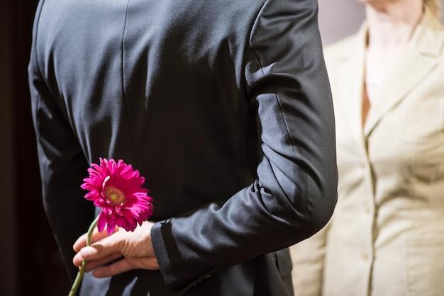 スーツを着た若い男は彼の背中の後ろにガーベラの花を保持します。