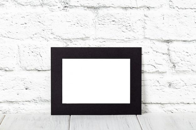木製のテーブルの上の水平の黒フォトフレーム。コピースペース付きモックアップ