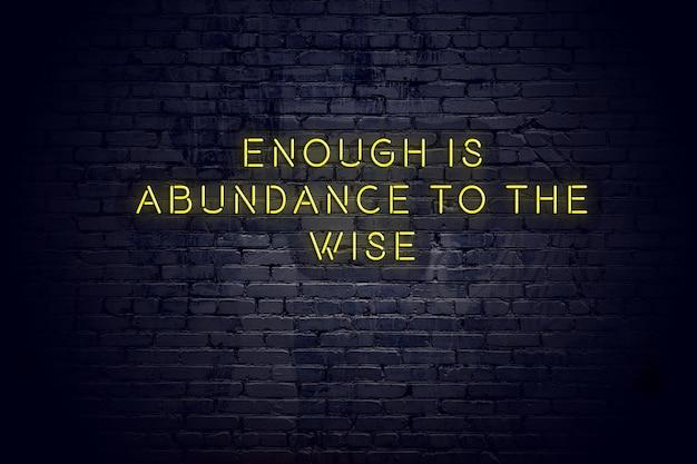 Неоновая вывеска с положительной мудрой мотивационной цитатой к кирпичной стене