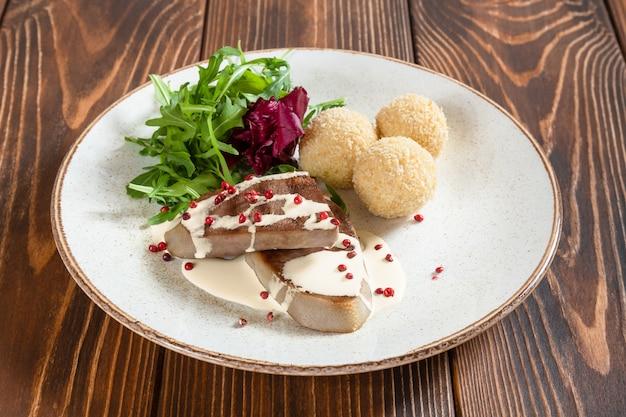 牛タンとクリーミーなソースのプレートとチーズのボールと素朴な木製のテーブルのロケットサラダ