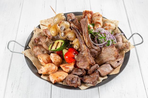 Ассорти из мяса, рыбы и овощей на металлическую чашу на белом деревянном столе