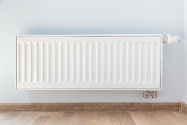 Деталь интерьера. белый металлический радиатор на белой стене