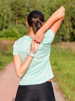 ドリルの前に彼女の腕を伸ばして若い女性ランナー