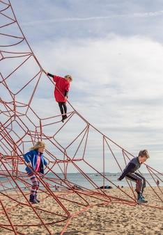 Дети играют на детской площадке с веревками на пляже барселоны, испания
