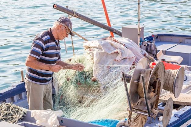 Сиракузы, италия: старший рыбак распутывает сеть на лодке