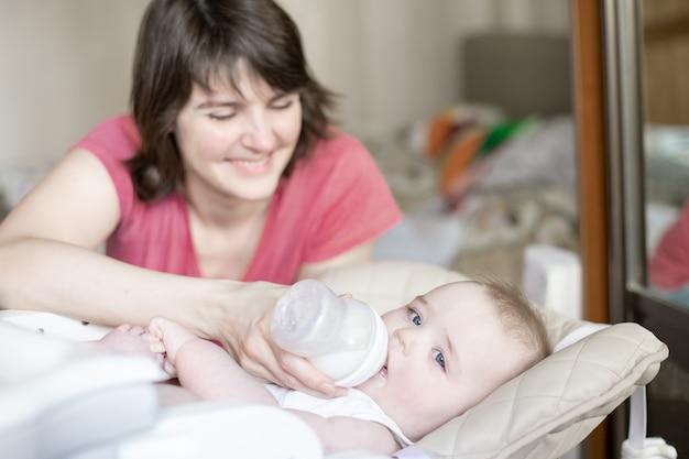 美しい若い母親は瓶から彼女の赤ちゃんを供給