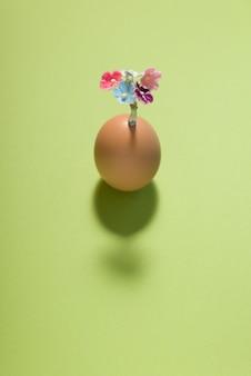 緑色の背景で豪華な花のコサージュと卵