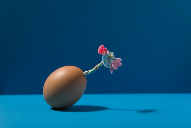 青い背景に豪華な花のコサージュと卵