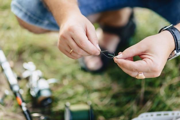 漁師は夏に湖で鯉をキャッチするためのスナップを準備します