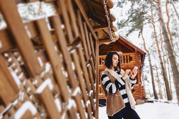 冬の森の木造コテージに対してのチョッキで携帯電話を持つ少女