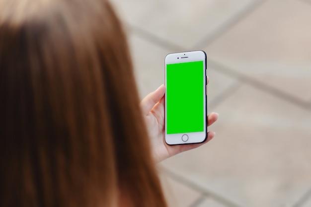Телефон в аккуратных руках девушек с зеленым экраном