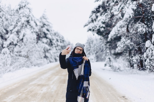 Красивая девушка делает селфи посреди снежной лесной дороги