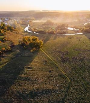 Сельская местность с лесом и рекой в тумане на осенней антенне