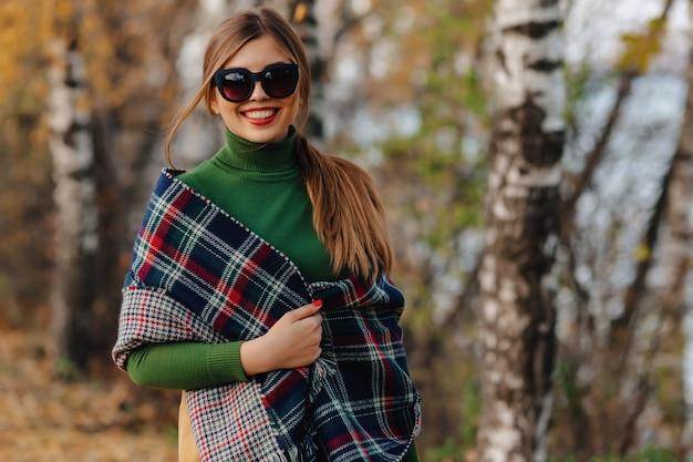 Уютная стильная прогулка молодой девушки в осеннем красочном парке в солнечных очках