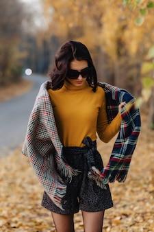 サングラスで秋のカラフルな公園で居心地の良いスタイリッシュな若い女の子の散歩