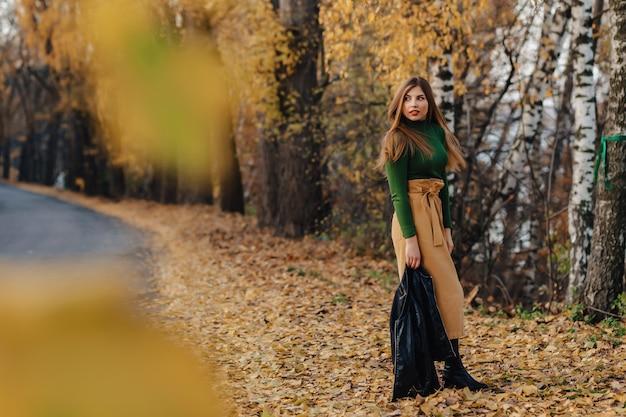 秋の公園で居心地の良いスタイリッシュな若い女の子の散歩