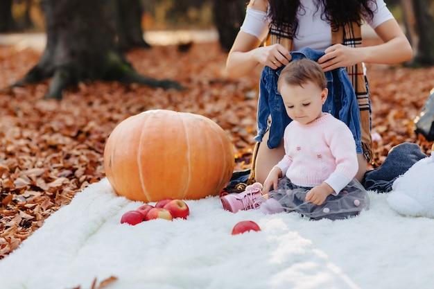 Маленький милый ребенок в парке на желтый лист с тыквой осенью
