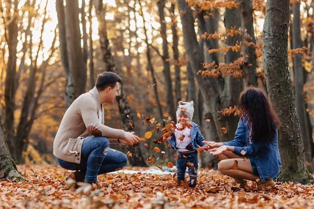 秋の大きなカボチャと黄色の葉の上の公園で小さなかわいい子と幸せな家庭