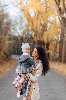 Игра мамы молодой женщины с маленькой дочерью на дороге парка осени