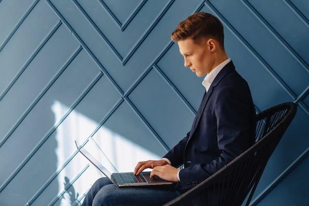 ラップトップ、青年実業家、フリーランサーの仕事、アクアの背景を持つスタイリッシュな若い男