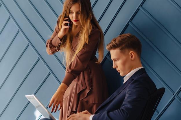 ラップトップと電話を持つ少女一緒にスタイリッシュな若い男、青年実業家
