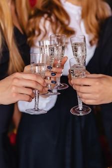 Большая компания празднует новый год с бокалами шампанского