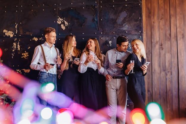 Большая компания празднует новый год с бокалами шампанского с телефонами мания