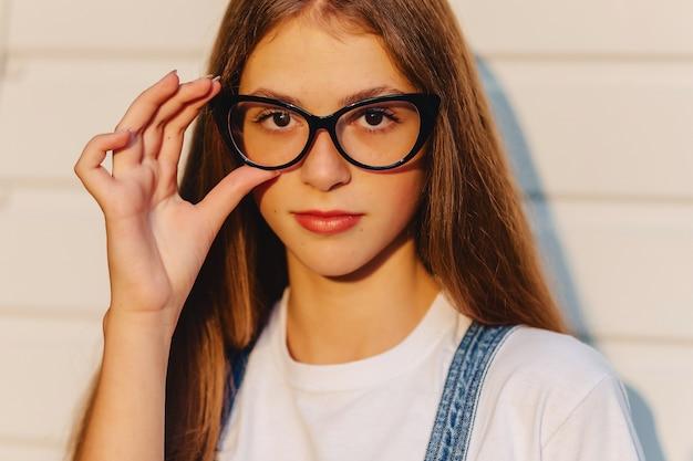 朝の日差しでスタイリッシュなメガネの若い肯定的な魅力的なかわいい女の子