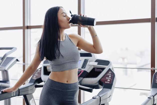 Девушки в спортзале тренируются на беговой дорожке и пьют воду