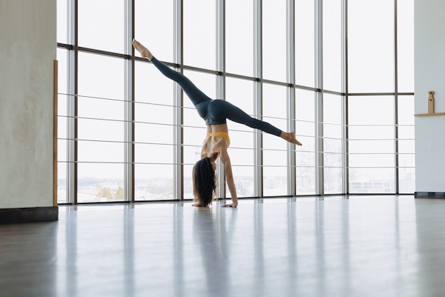 床にヨガのフィットネス演習をやっている若い魅力的な女の子。パノラマ窓