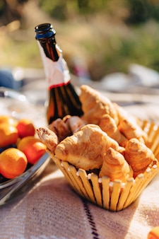 フルーツ、ワイン、紅茶、カップ、クロワッサン、お菓子の敷物の上の夏のピクニック