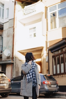 車の建物の背景にコートを着たメガネをかけて魅力的な肯定的な若い女の子