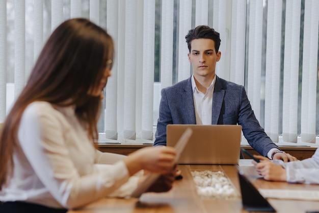 近代的なオフィスのスタイリッシュな若者たちは、書類とノートパソコンを片方の机で仕事