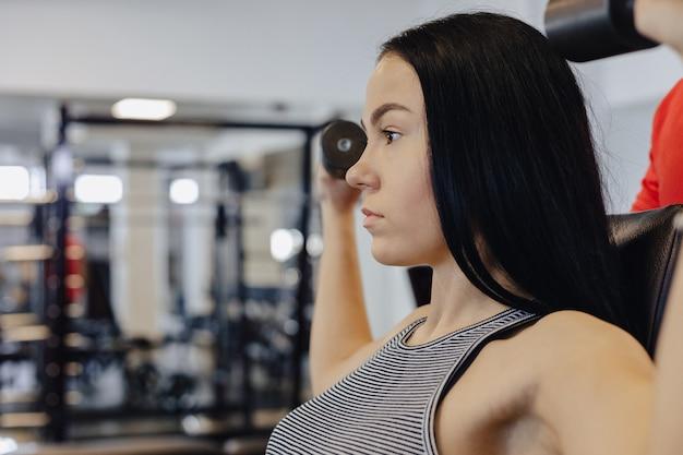 ジムでスポーツウェアを着た若い女の子がダンベル体操を行い、コーチは彼女を助けます