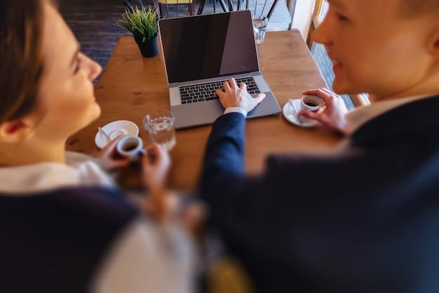 スタイリッシュなカップルはカフェで朝のコーヒーを飲み、ラップトップで動作します