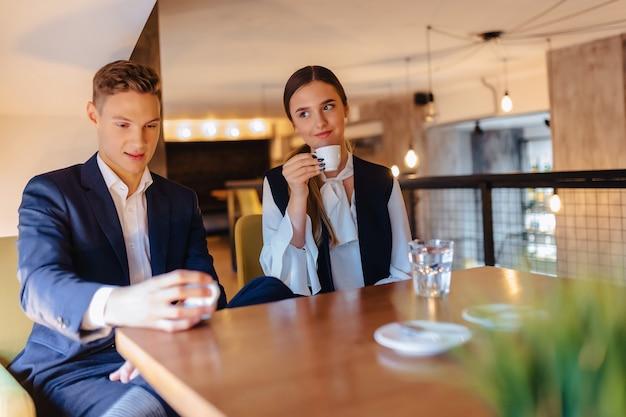 スタイリッシュなカップルは、カフェ、若いビジネスマン、フリーランサーで朝のコーヒーを飲みます