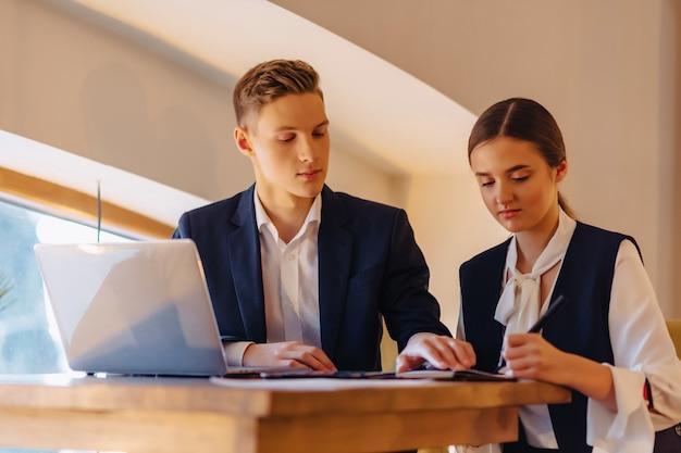 若いビジネスマンの男の子と女の子がノートパソコン、タブレット、カフェでメモを扱う