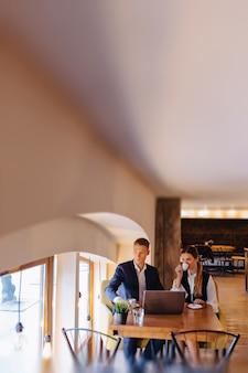 スタイリッシュなカップルはカフェで朝のコーヒーを飲み、ノートパソコン、若手ビジネスマン、そしてフリーランサーと協力しています。